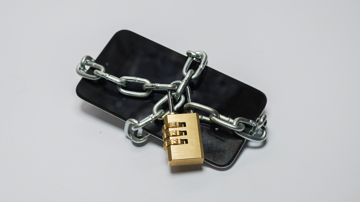 A cellphone wrapped in a chain with a padlock.
