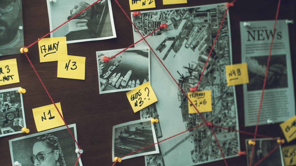 Detective board with photos of suspected criminals, crime scenes, and evidence connected with red thread