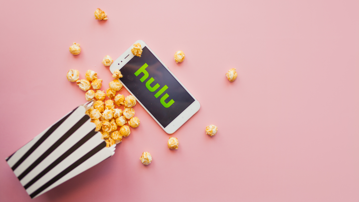 Hulu app open on smartphone next to box of popcorn scattered on floor
