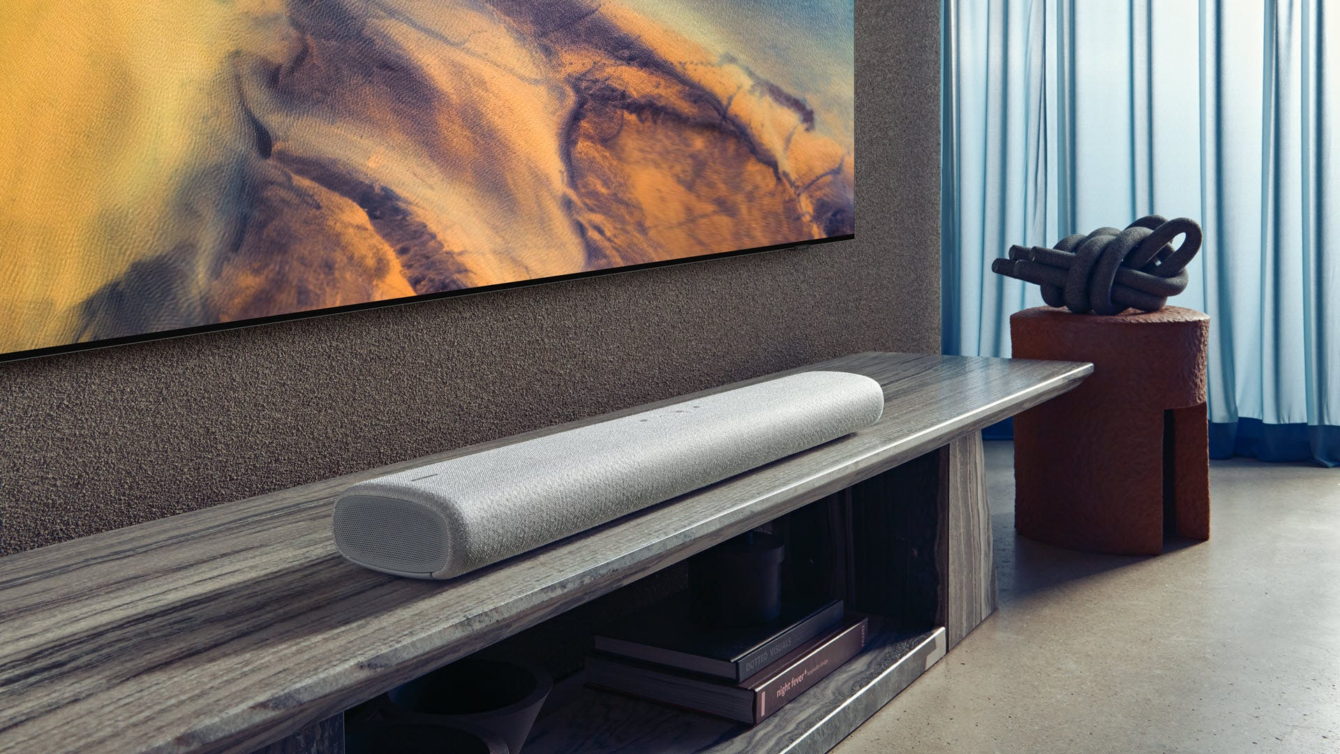 A sleek soundbar beneath a tv.