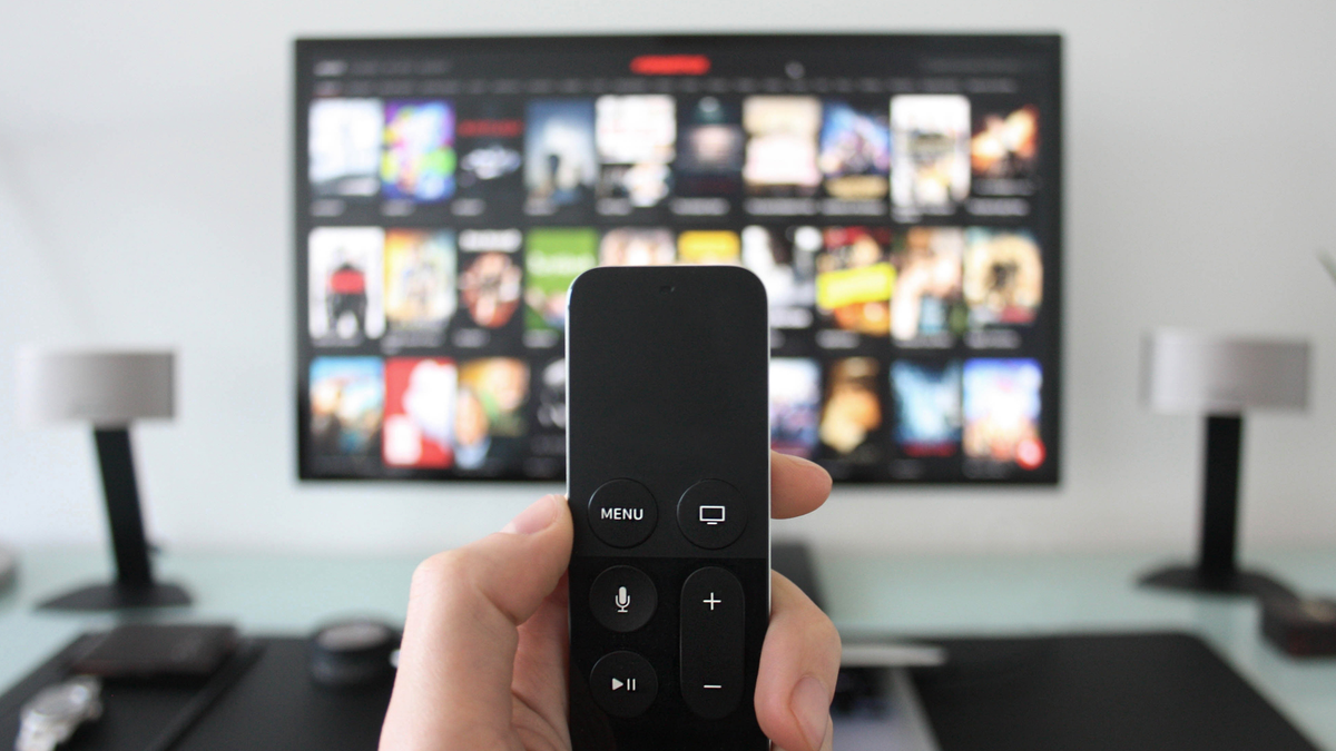 Hand holding a TV remote while searching for shows on a streaming TV service