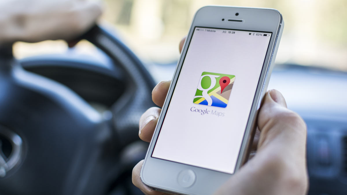 Google Maps app logo open on phone in car with steering wheel in the background
