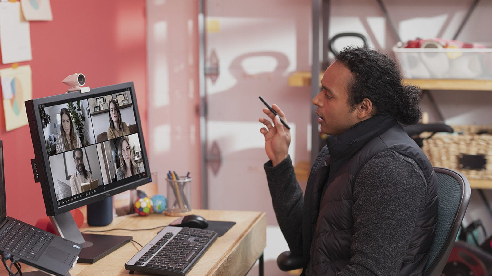 A man on a video call using a small white webcam.