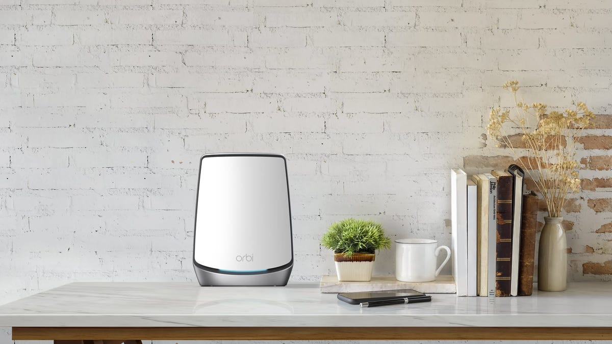 An Orbi Wi-Fi 6 Router on a counter by some books.