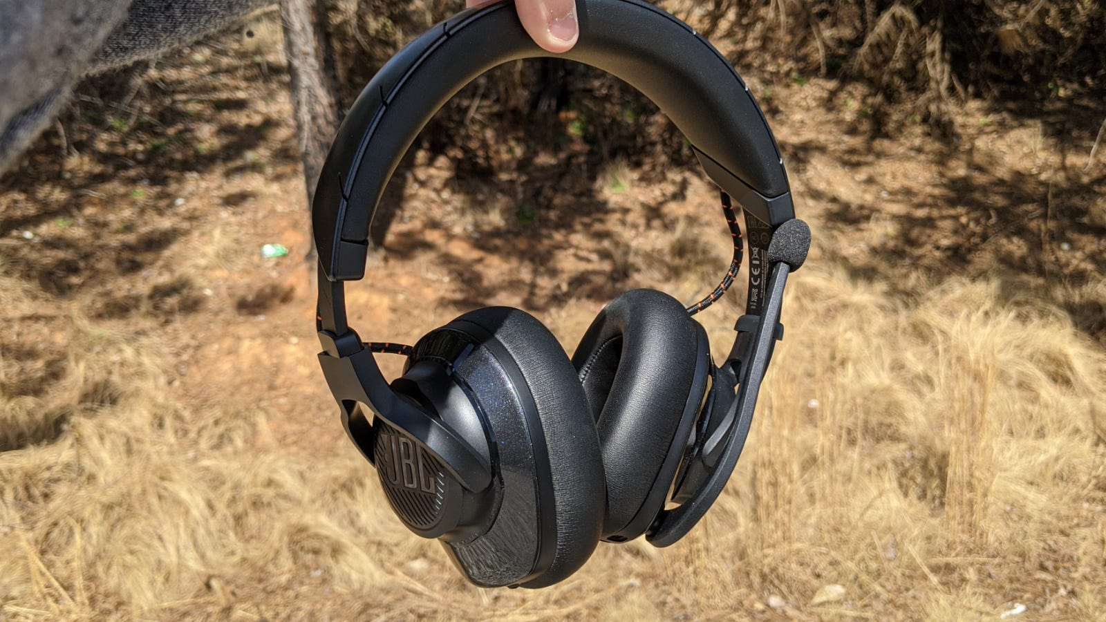 JBL Quantum 600 Headset held up against a forest backdrop
