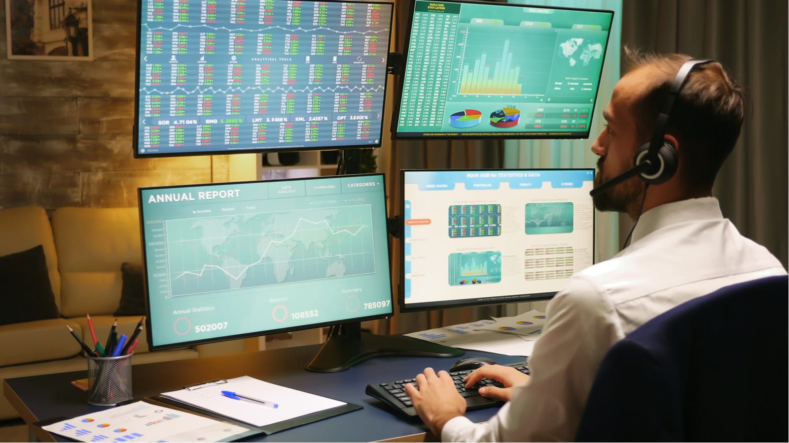 Stock trader operating multiple monitors stacked on top of each other