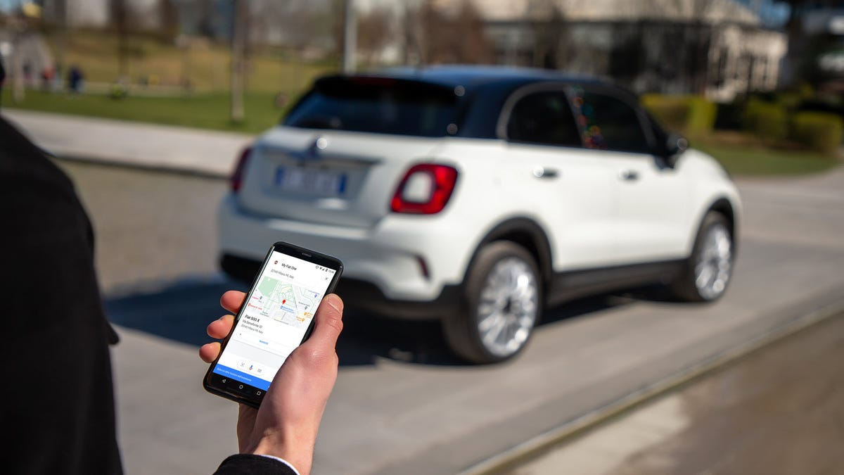 A man looking at Google Assistant on his phone in front of a Fiat Car