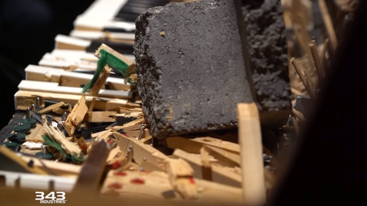 A broken piano keyboard, with a giant rock laying on the destroyed keys.