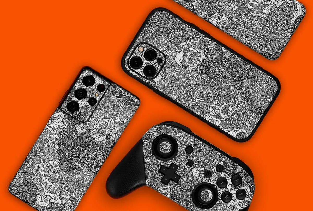 An iPhone, Samsung Phone, Pixel, and Nintendo Switch controller covered in Robot Camo skins.