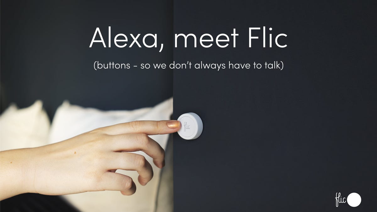A white button with the Flic logo in a bedroom.