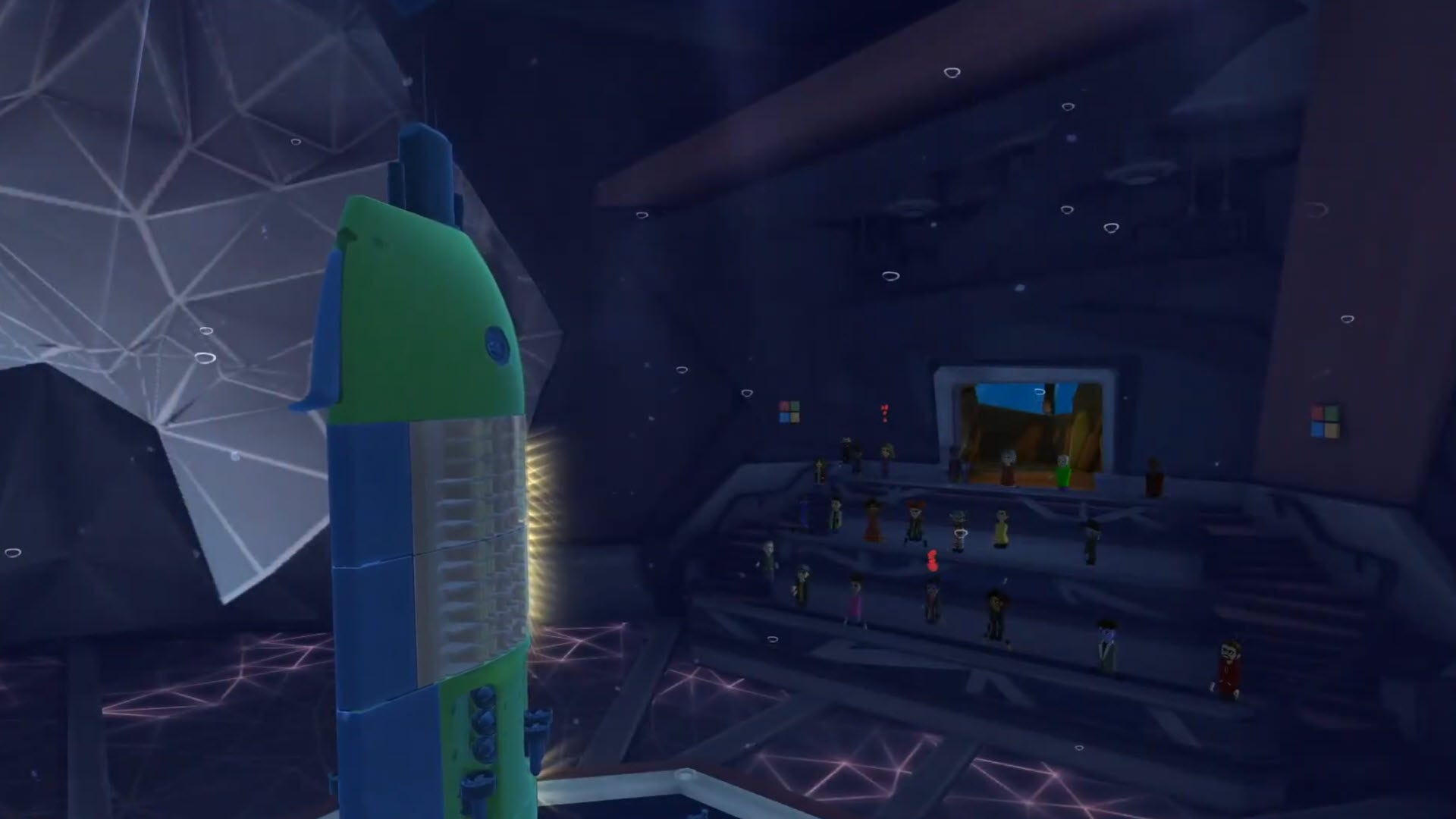 A digital submarine rising from a stage in front of a group of digital avatars.