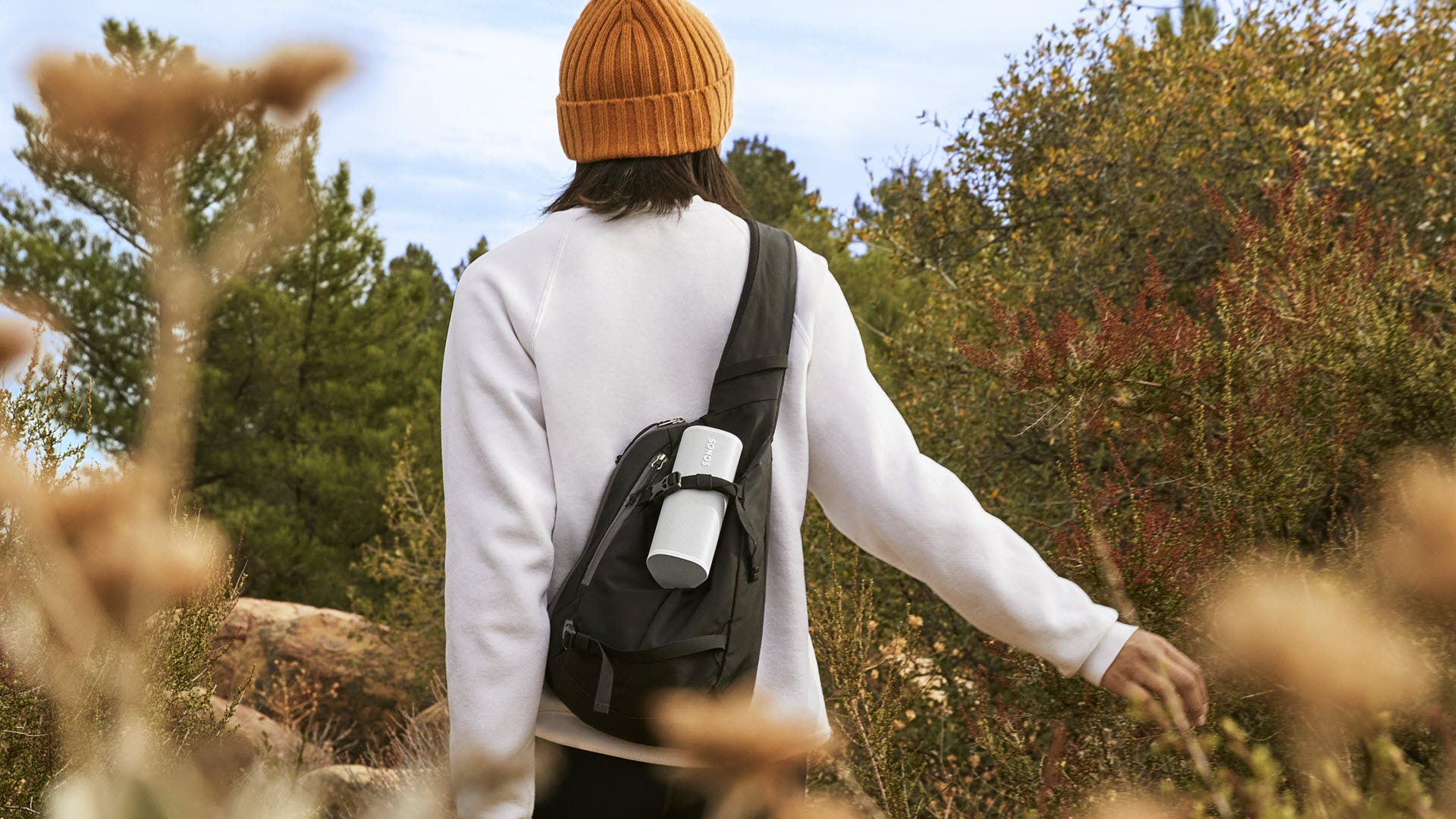 A Sonos Roam speaker strapped to a sling bag.