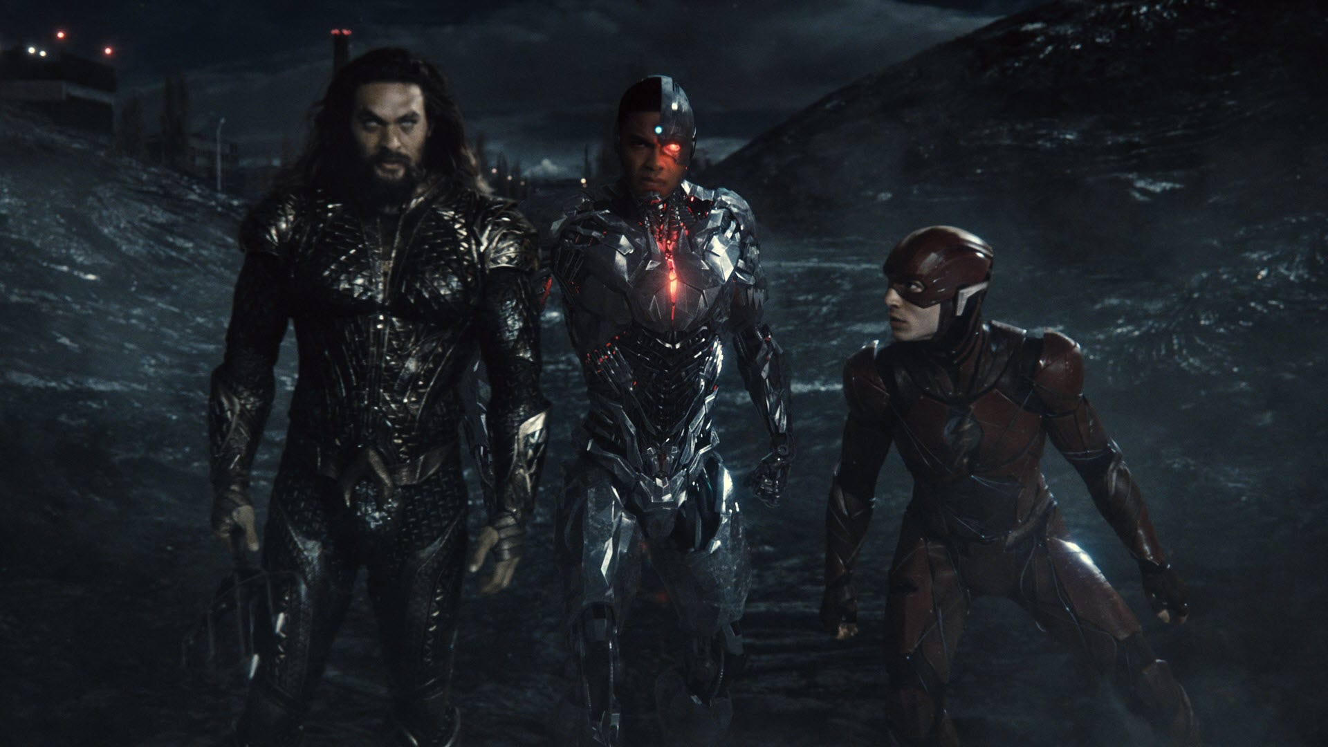 Aquaman, Cybord, and Flash in a darkened landscape.