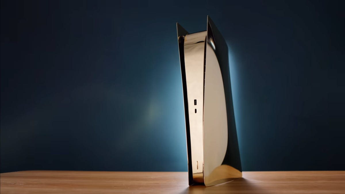 A Brass PlayStation 5 on a wooden desk.