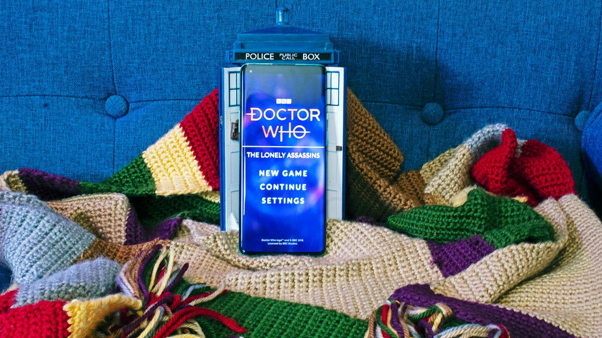 """A phone with the """"Doctor Who: Lonely Assassin"""" game in front of a Tardis and on a 12 foot long multi-colored scarf."""