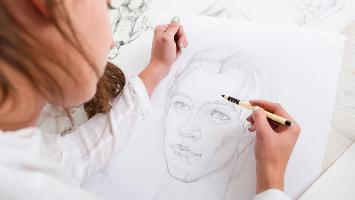 Artist drawing pencil portrait close-up.
