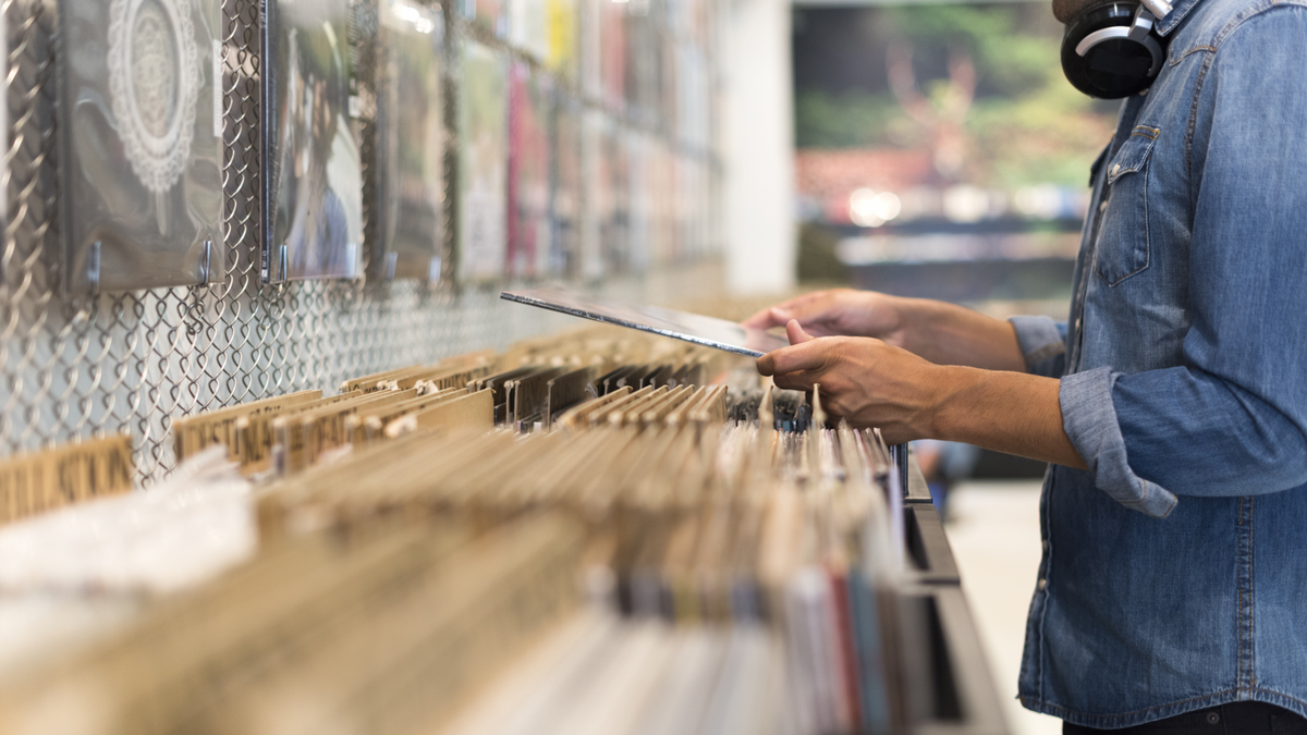 Person browsing vinyl albums at a record store