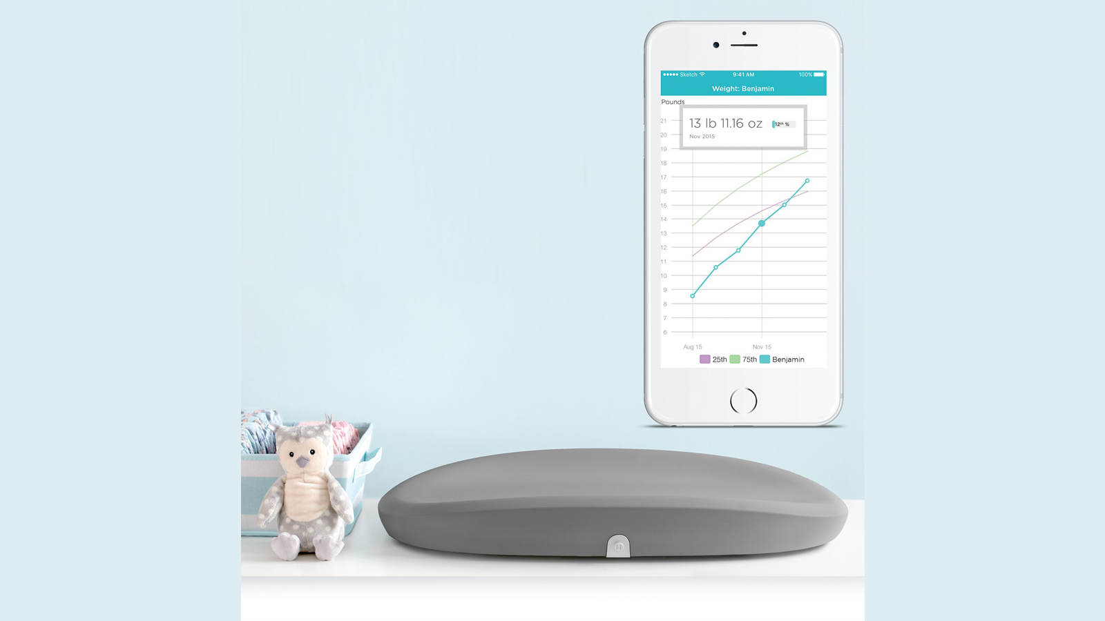 Hatch Baby Grow Smart Changing Pad on the table next to cute baby toys and accompanying mobile app on smartphone