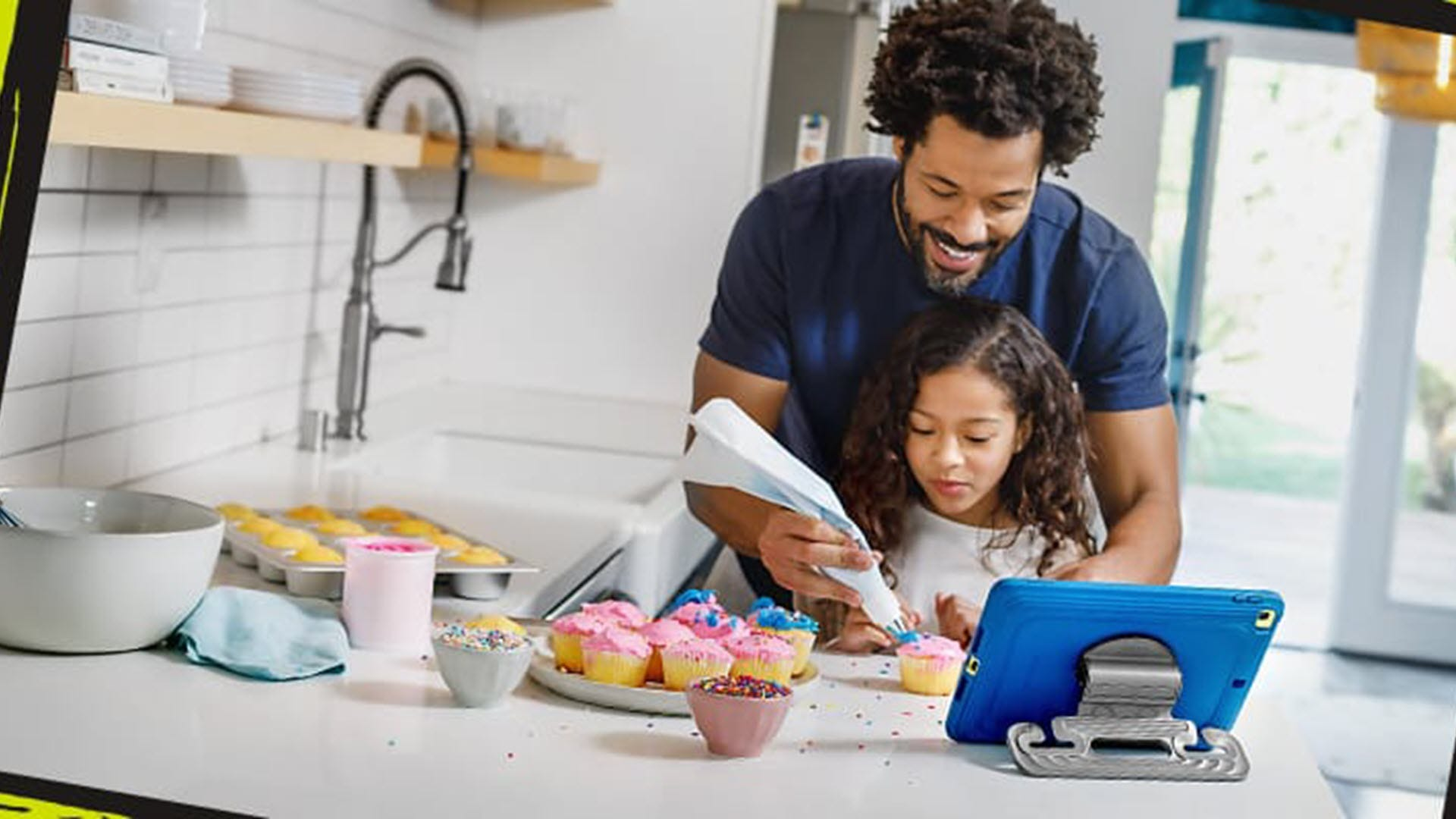 A father and daughter decorating cupcakes in front of an iPad held in a kid friendly case.