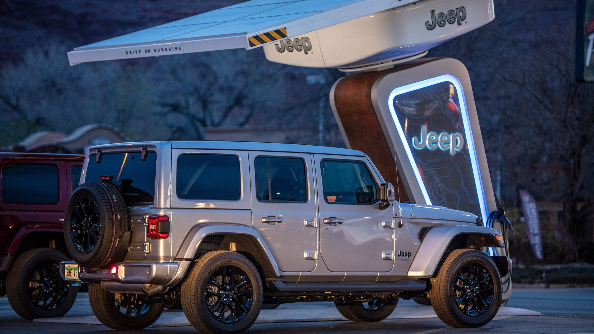 A Jeep beneath a solar roof with Jeep logos.
