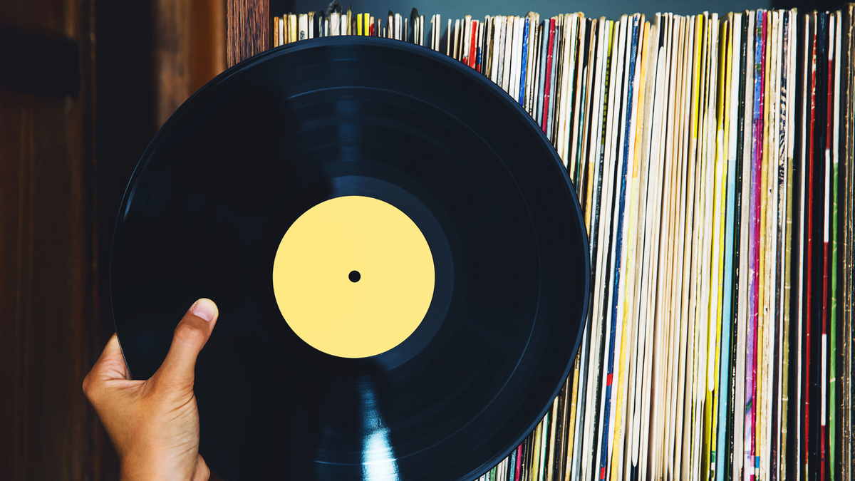 Person's hand holding a vinyl record in front of a collection of albums