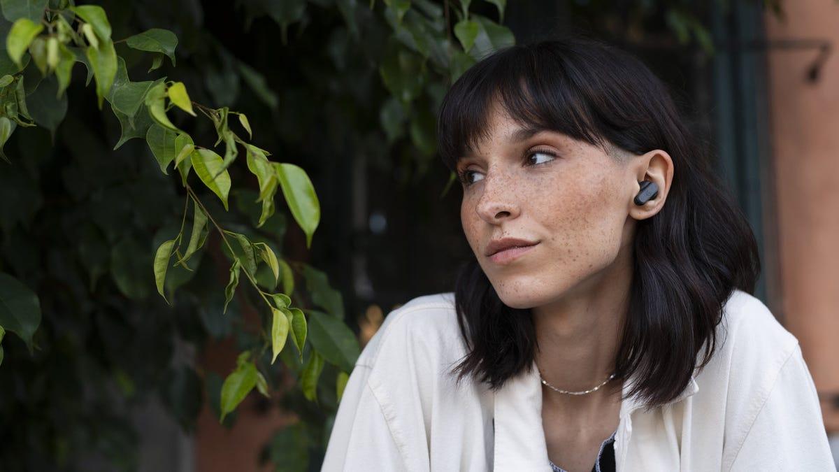 Egy nő, fekete fekete vezeték nélküli fülhallgatóval.