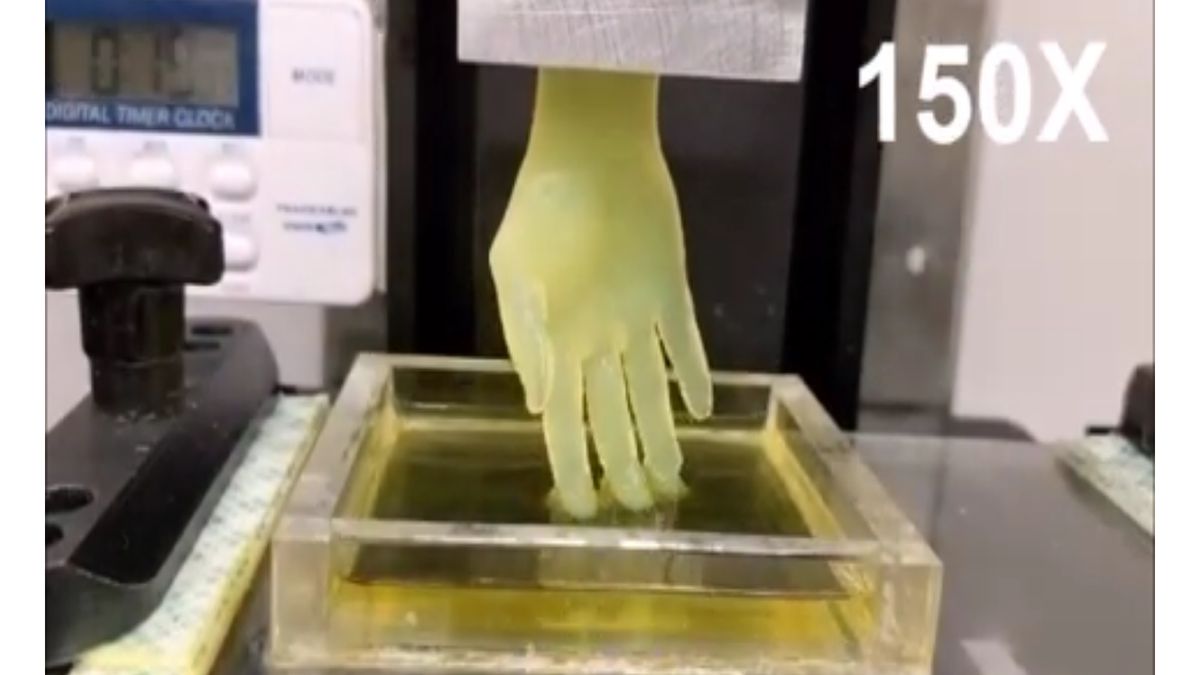 A 3D printed hand rises from a hydrogel solution.
