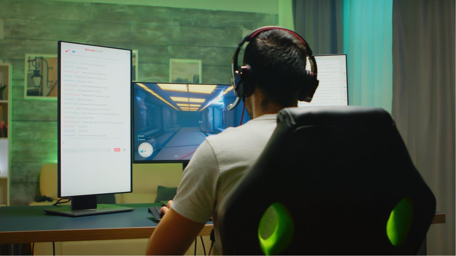 Man using three monitor desk setup