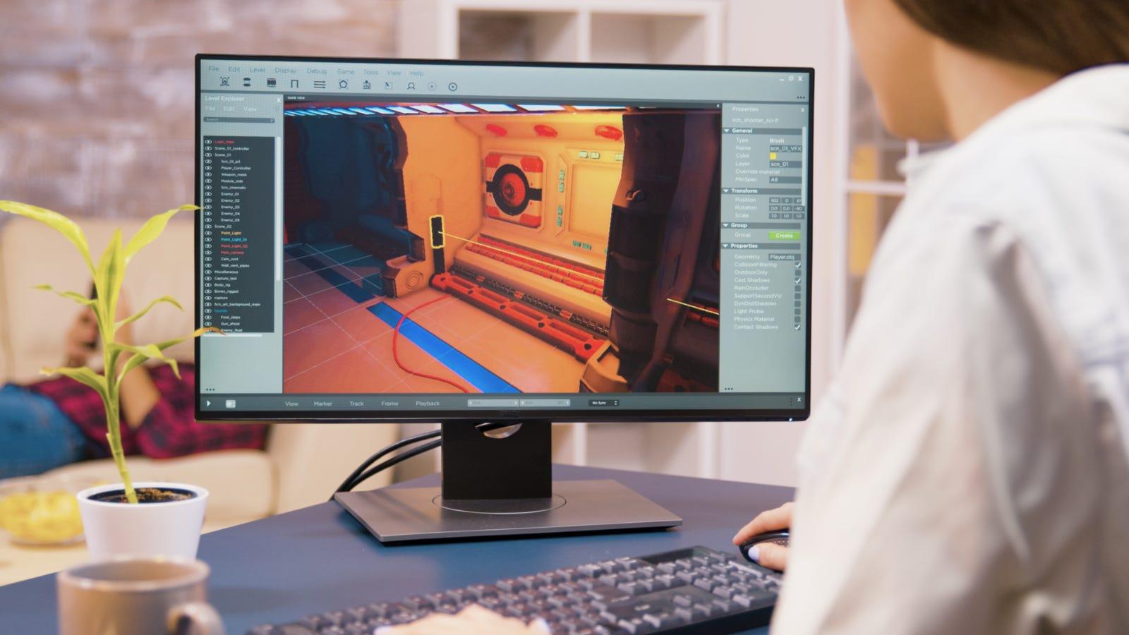 Persona che utilizza un programma di sviluppo di giochi su un monitor