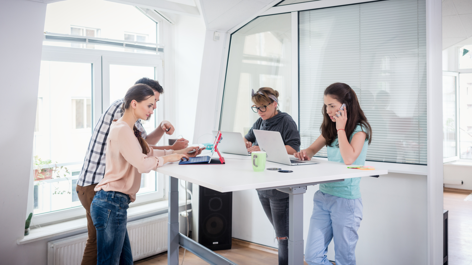 Busy coworkers using mobile technology while sharing a standing desk in a modern office space