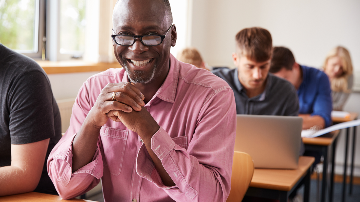 Adult student sitting in class at desk smiling