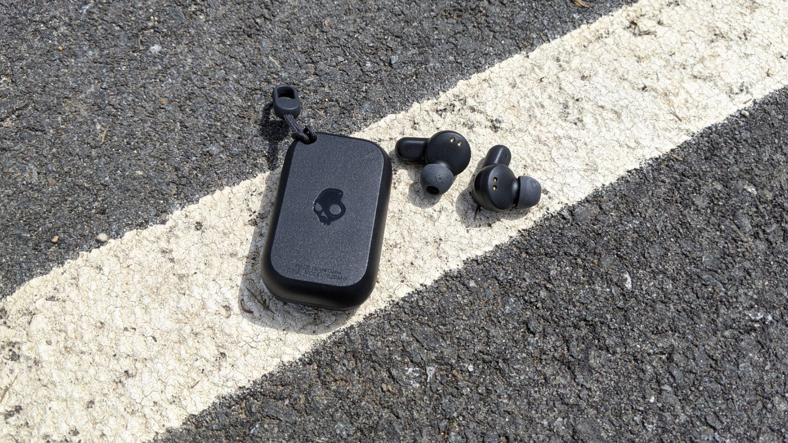 Skullcandy Dime case and earbuds separated on pavement
