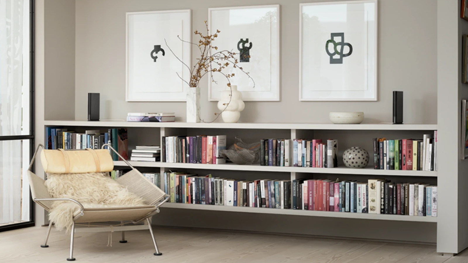 Two Bang & Olufsen BeoSound Emerge speakers on low, wide bookshelf