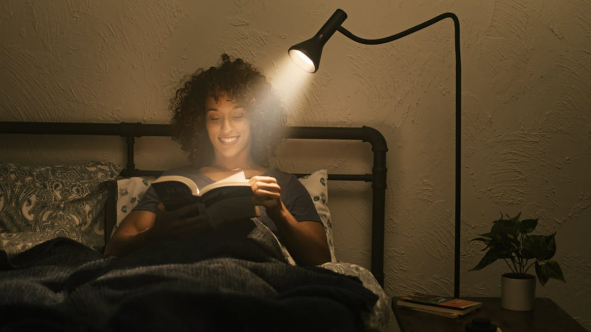 A woman reading a book under a task light.