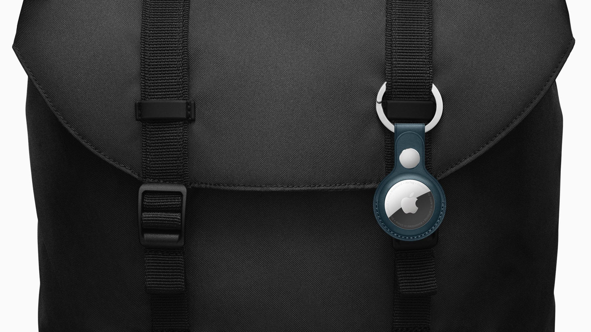 An AirTag attached to a backpack.