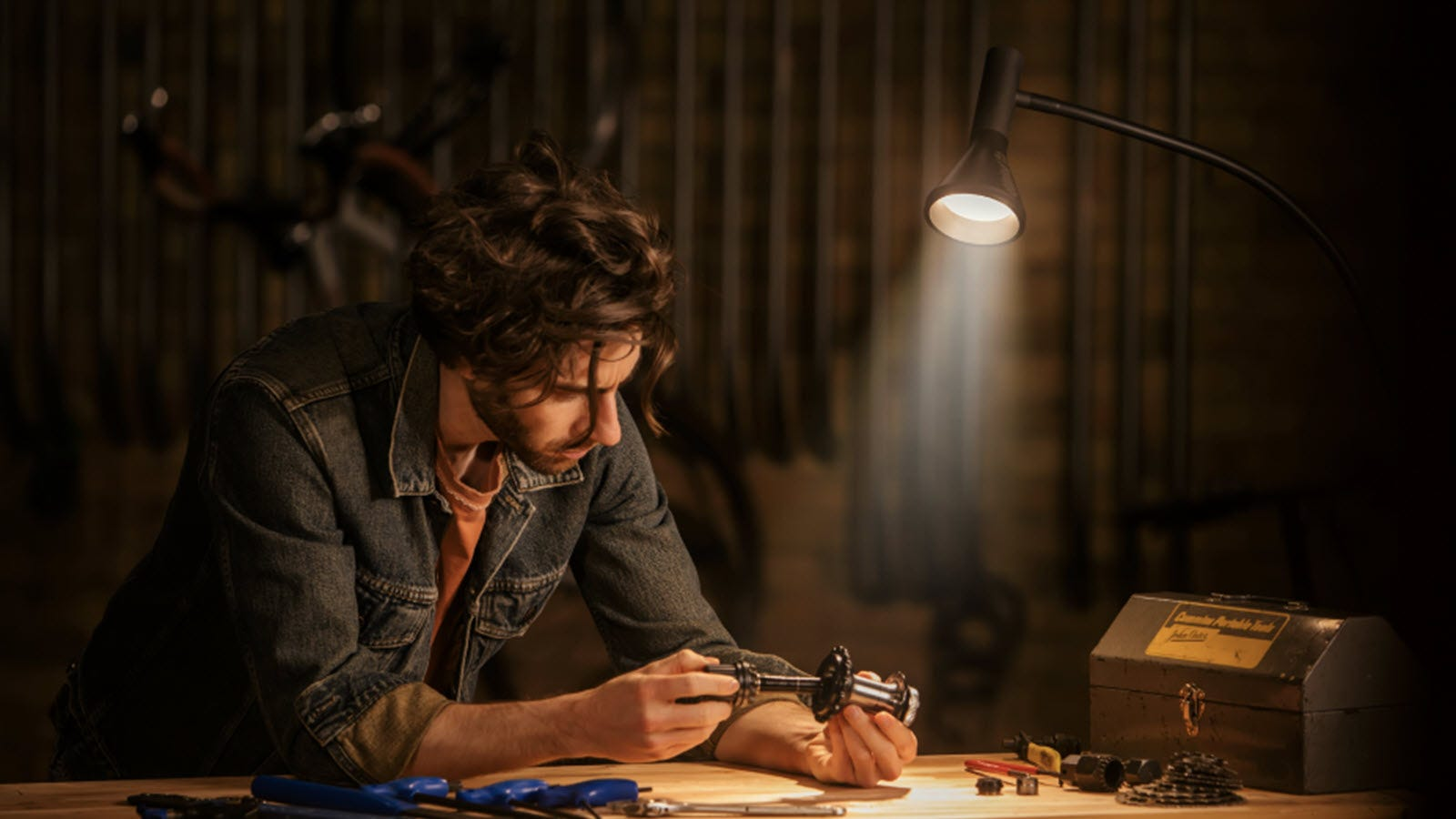 A man working on a toolbench under a floor lamp.