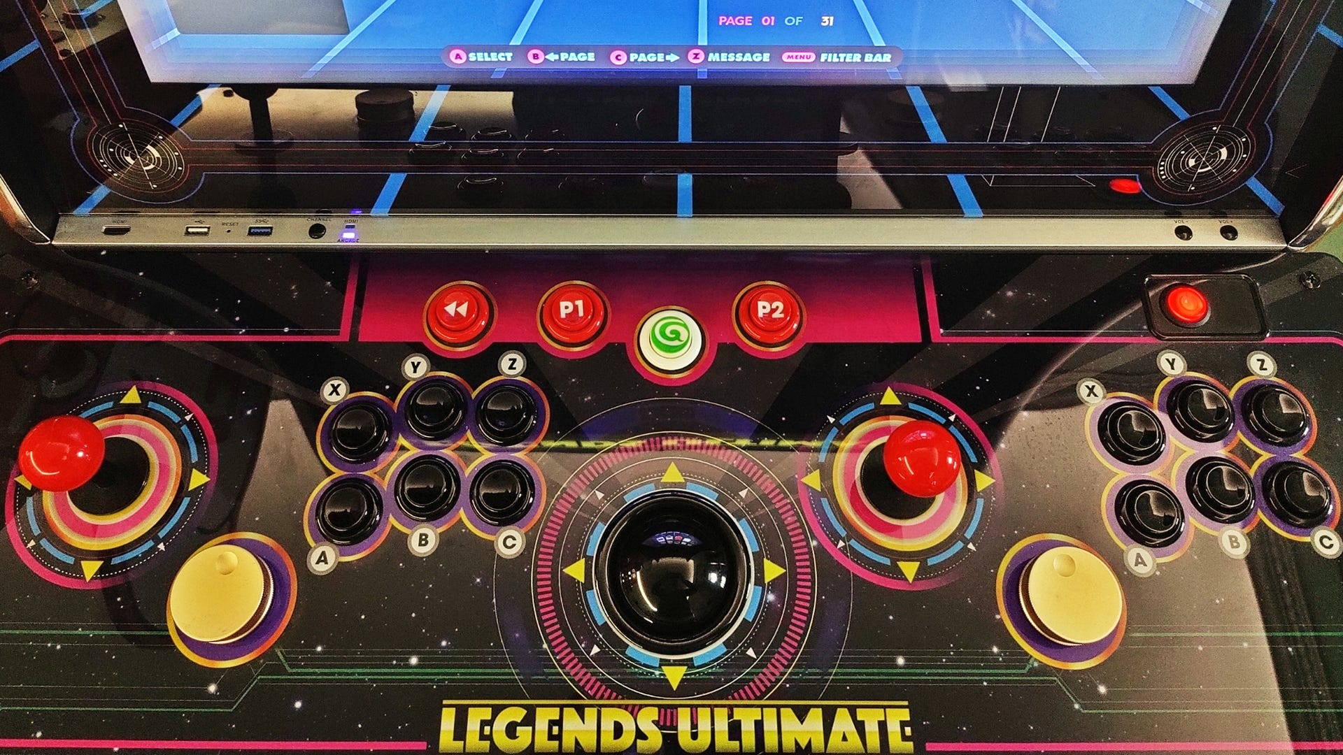 A top down view of the Legends Ultimate control deck, with two joysticks, 12 buttons, two spinners, and a trackball.