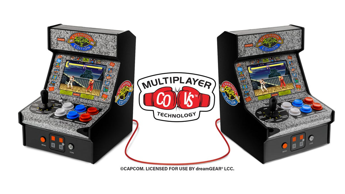 Two 'Street Fighter II' arcades hooked up to each other through a cable.