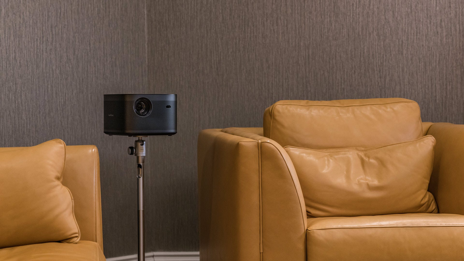 A projector mounted on a stand in a living room.