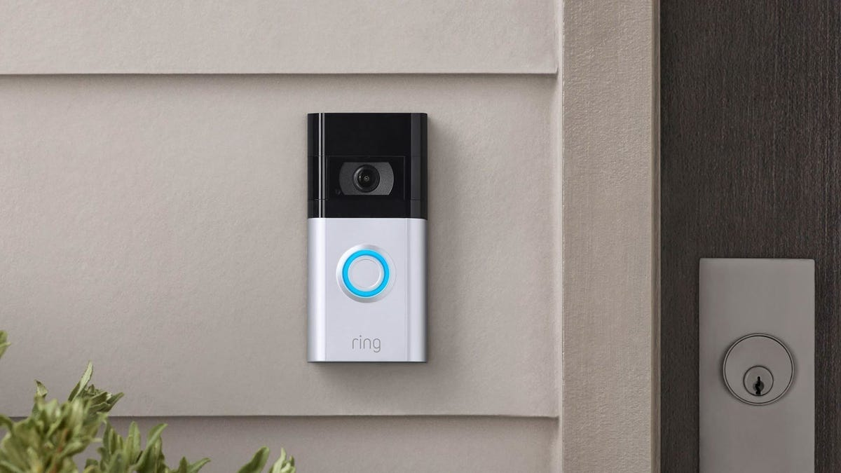 Ring doorbell camera mounted on home siding next to a door.
