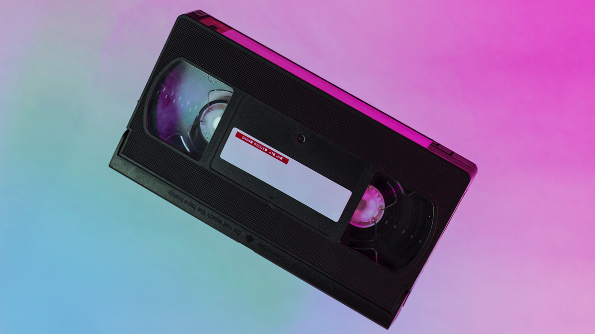 A VHS tape on a soft, colorful background.
