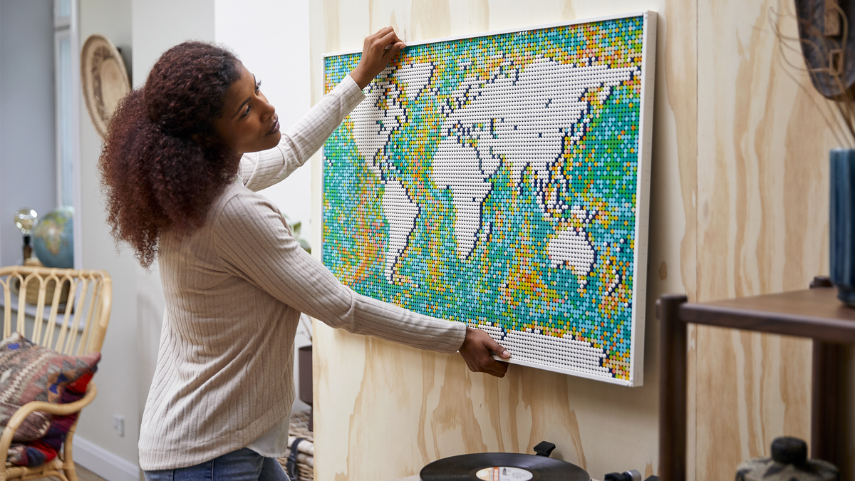 Person attaching his completed LEGO Art World Map to the wall in a room with worldly decorations