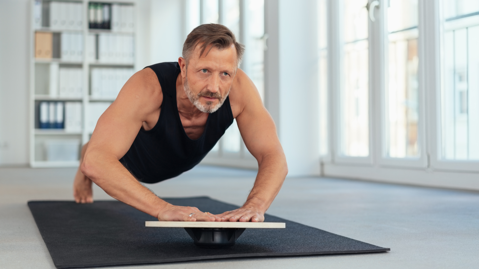 Middle-aged fit person exercising a plank variation with hands on a balance board indoors