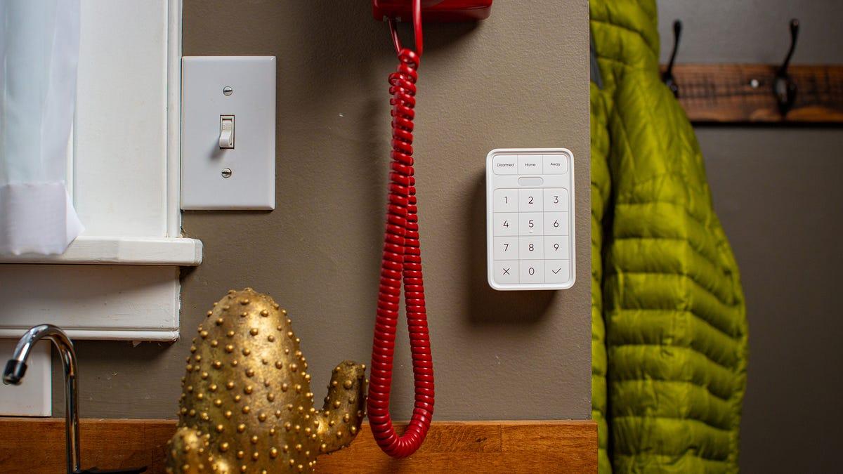 A Wyze keypad next to a coat rack.