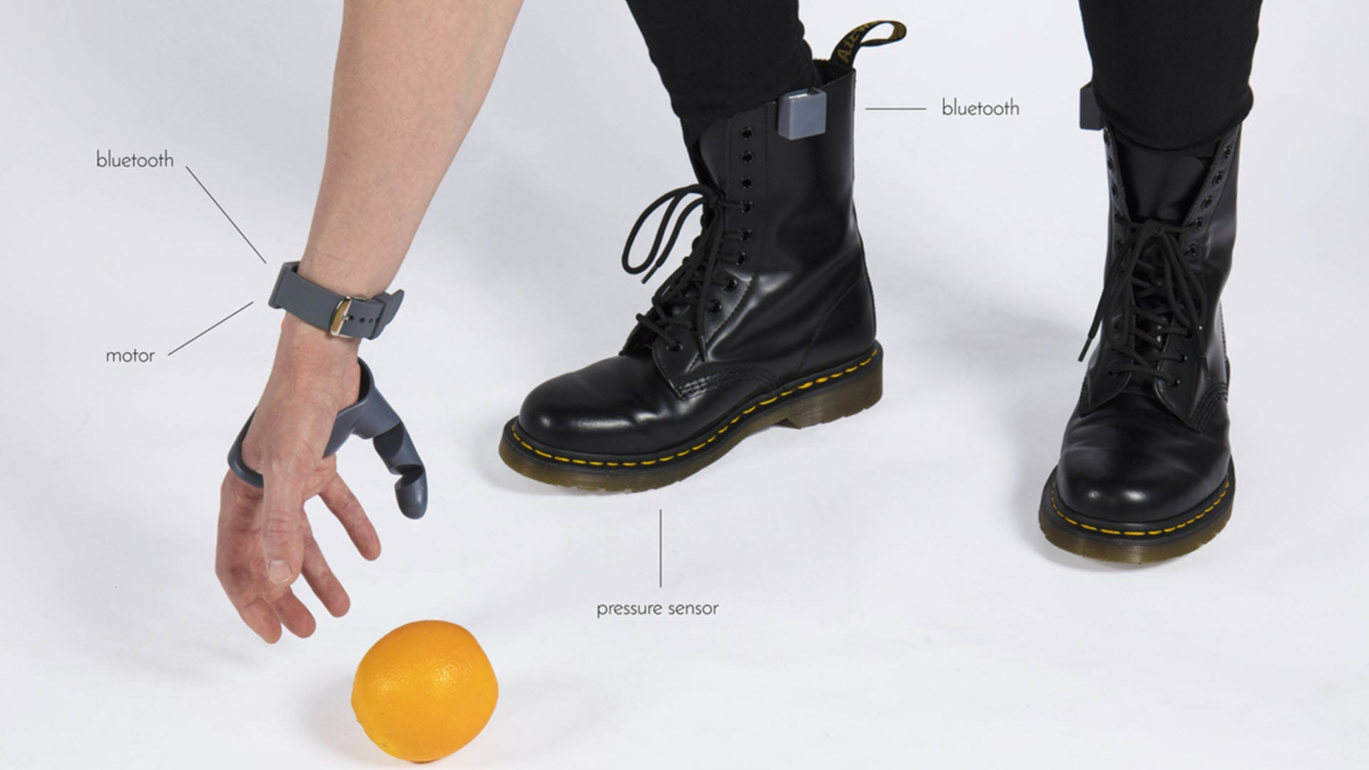 A man reaching down for an orange with two thumbs, and wireless sensors connected to his boots.