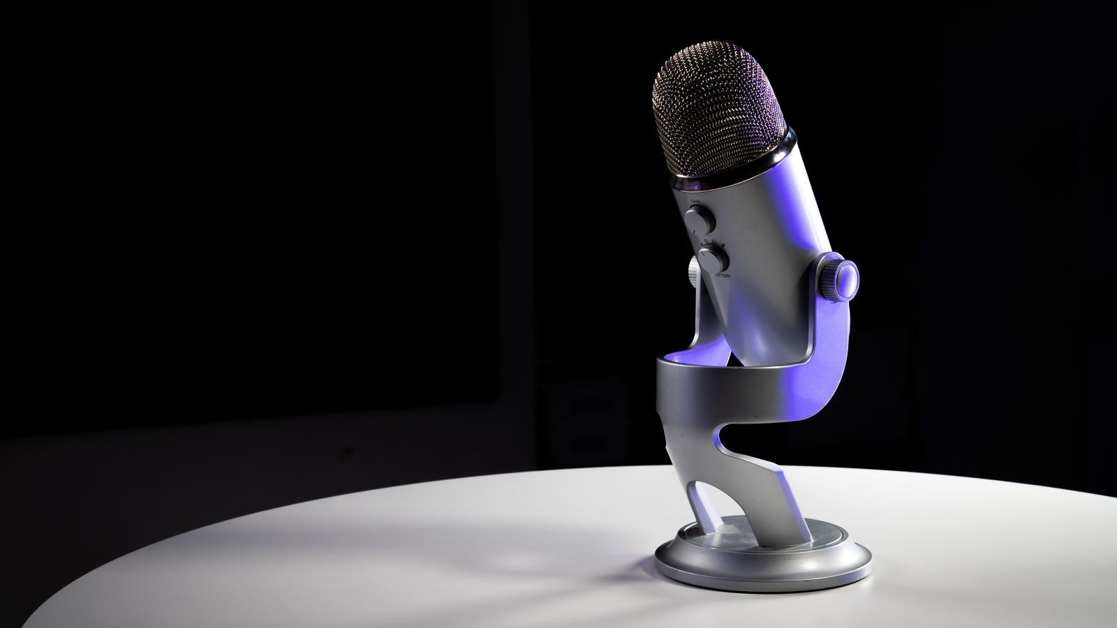 Микрофон Blue Yeti на серебряном столе на черном фоне