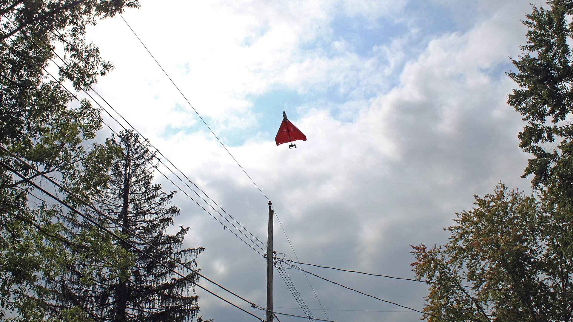 An RC Paper plane flying high in the sky towards power lines.
