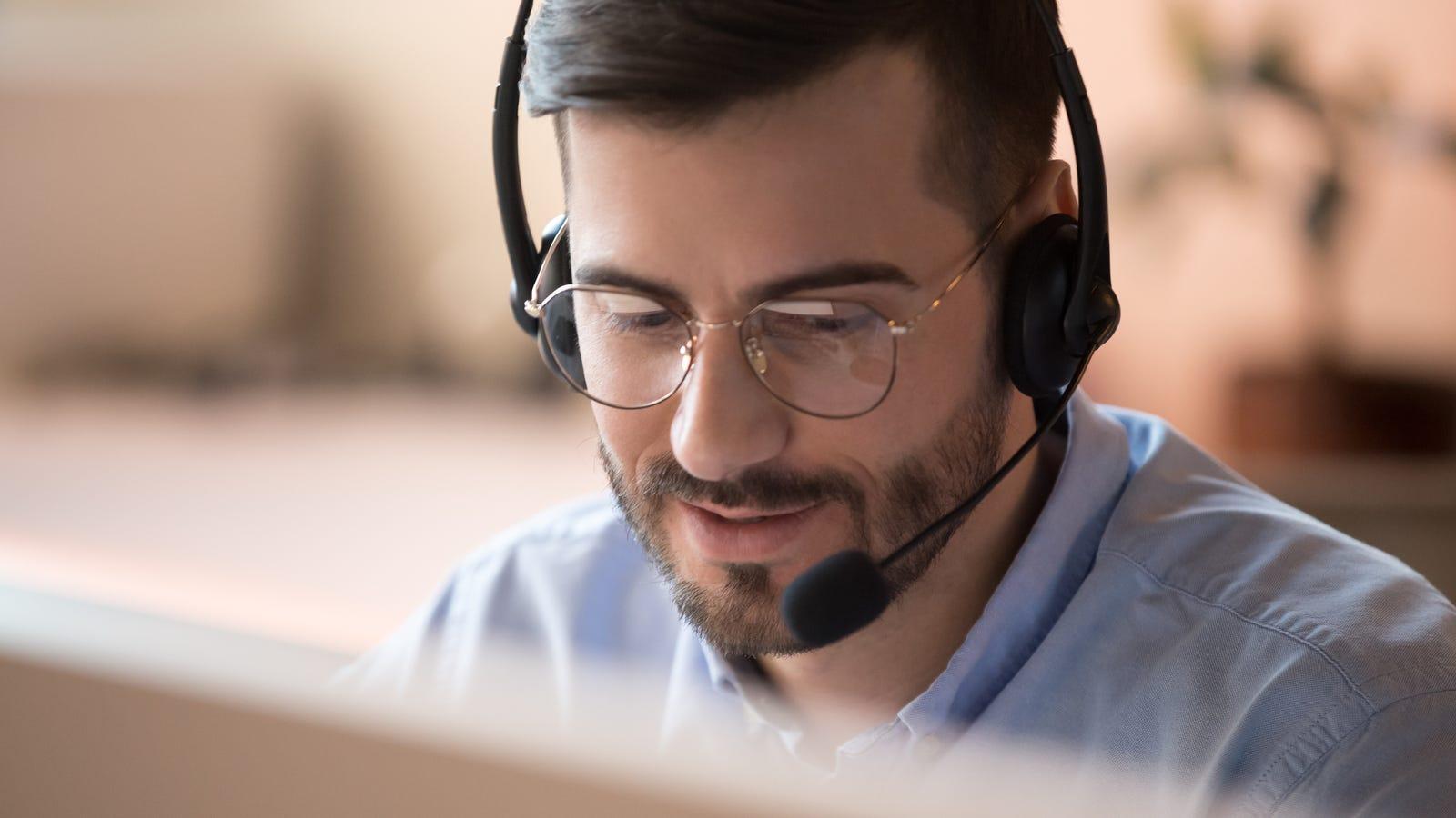 Человек, носящий гарнитуру во время использования компьютера
