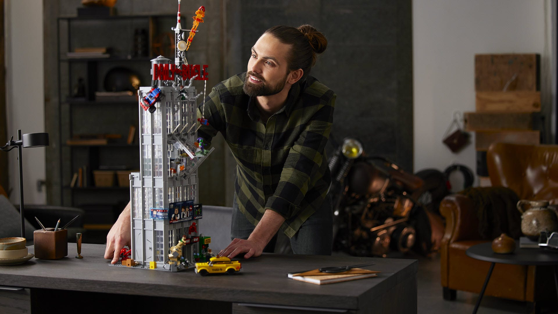 A man standing next to a nearly three-foot-tall LEGO Daily Bugle set