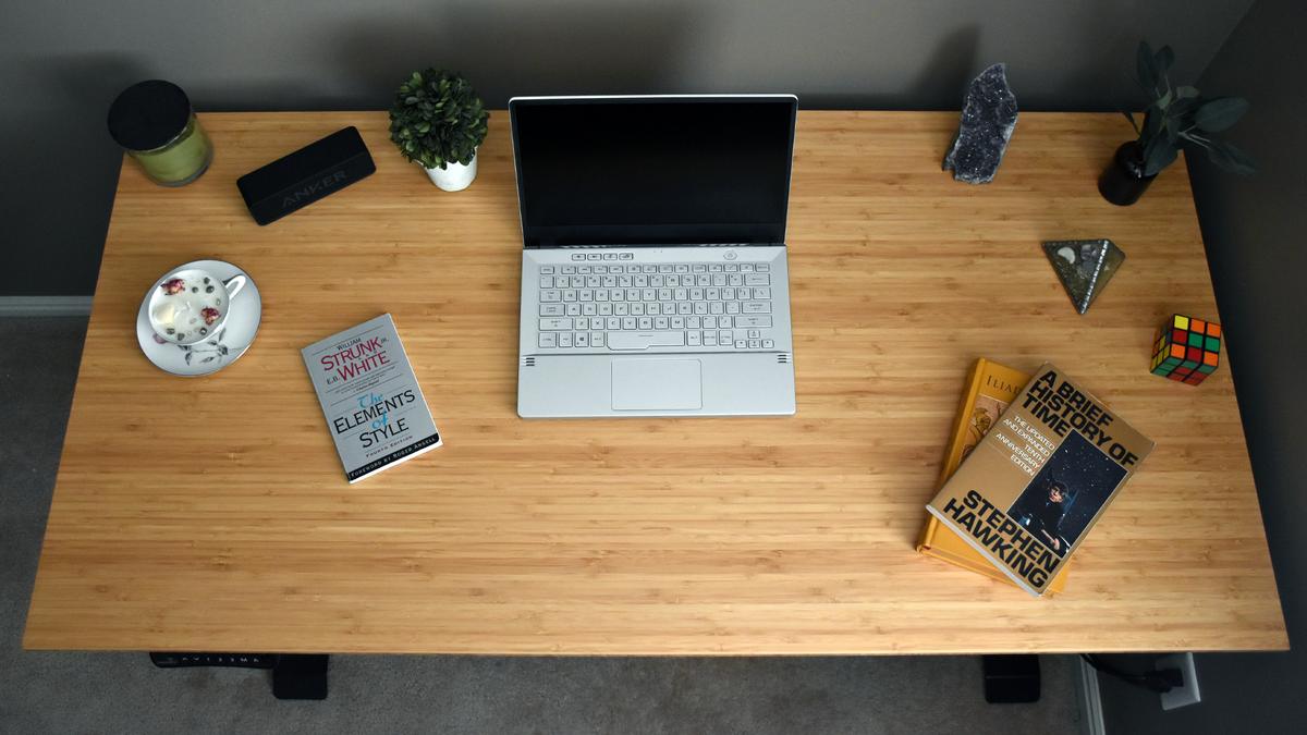 Вид сверху на постоянный стол Flexispot Kana Bamboo с книгами, ноутбуком и другими безделушками